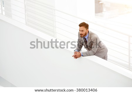 Thoughtful young male CEO thinking about growth his career while standing in modern office hallway, serious man manager looking away during rest in work break after big presentation of new project - stock photo