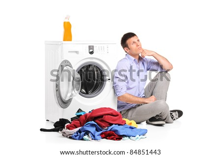 Thoughtful young male sitting next to a washing machine isolated against white background - stock photo