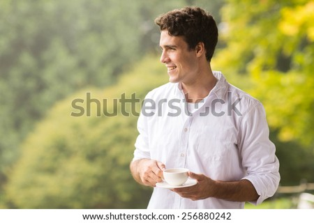 thoughtful young man having cup of coffee outdoors - stock photo