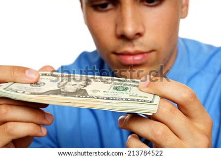 Thoughtful young man in blue shirt looking at banknotes - stock photo