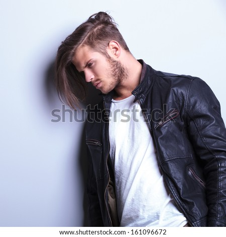 thoughtful young man in leather jacket, side view picture - stock photo