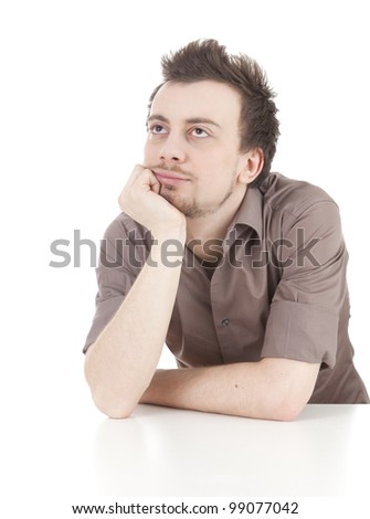 thoughtful young man leaning on the table, looking up, white background