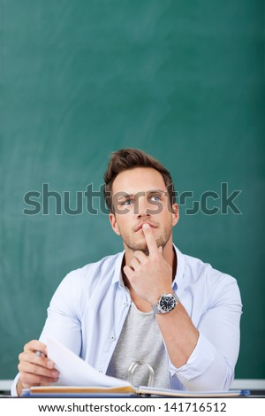 Thoughtful young man sitting in front of chalkboard with finger on chin - stock photo