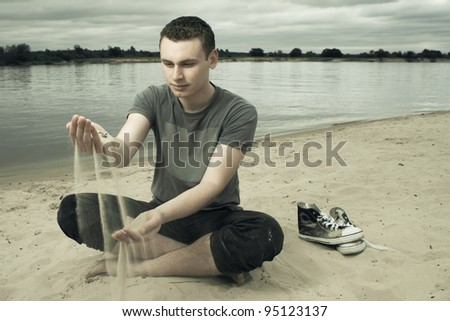 thoughtful young man sitting on the beach during stormy weather