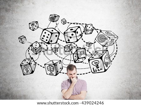 Thoughtful young man standing against concrete wall with connected dice sketch. Game and probability theory - stock photo