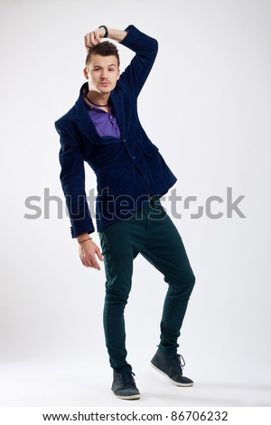 Thoughtful young man standing on studio background and scratching his head - stock photo