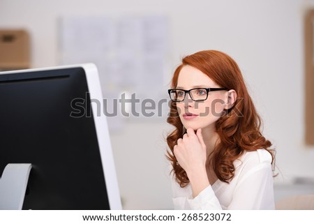 Thoughtful young redhead businesswoman wearing glasses reading her desktop monitor as she checks her work - stock photo