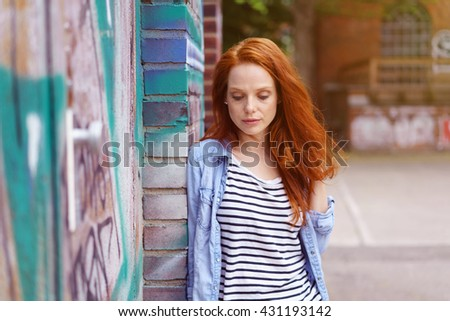 Thoughtful young redhead woman with downcast eyes standing outdoors leaning against a graffiti covered brisk wall looking down with a serious expression