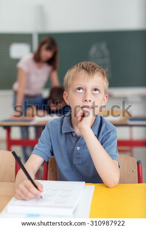 Thoughtful young schoolboy sitting in class at his desk writing in a school folder looking up into the air with a pensive serious expression, teacher in background - stock photo
