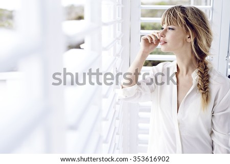 Thoughtful young woman at shutters