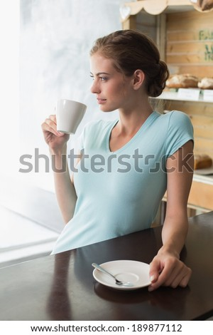 Thoughtful young woman drinking coffee at counter in the coffee shop - stock photo