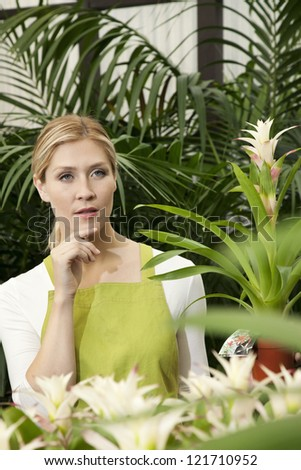 Thoughtful young woman in greenhouse - stock photo