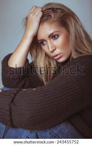 Thoughtful young woman in sweater looking away. Pretty young woman. - stock photo