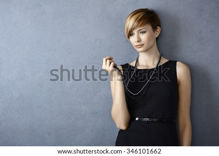 Thoughtful young woman looking at pearl necklace standing in front of grey wall - stock photo