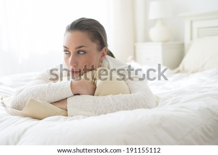 Thoughtful young woman looking away while lying in bed