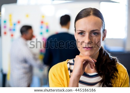 Thoughtful young woman with hand on chin while her colleagues discuss in the background - stock photo