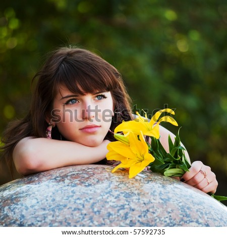 Thoughtful young woman with lily. - stock photo