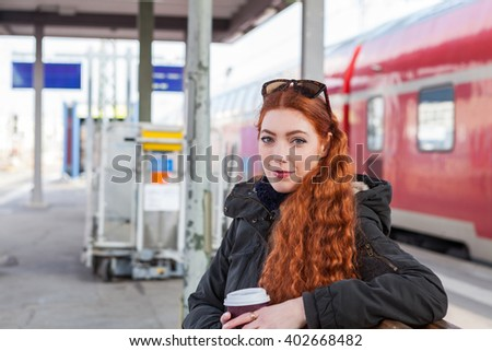 Thoughtful young woman with long red hair wears a coat and holds a coffee cup while waiting on a bench at a train station - stock photo