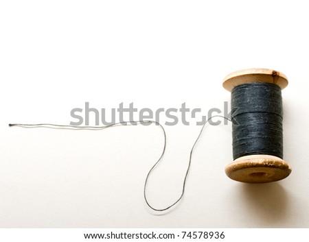 Thread bobbin on white background - stock photo