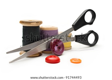 Thread bobbin, scissors and buttons on the white background - stock photo