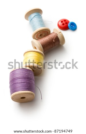 Thread bobbins and buttons on the white background - stock photo