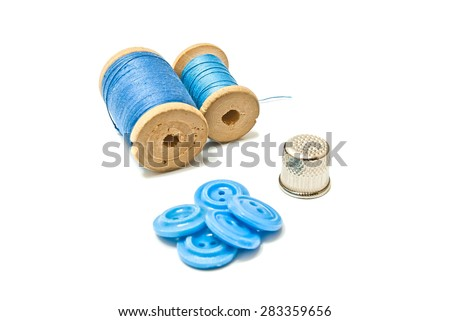 thread, buttons and thimble closeup on white background - stock photo