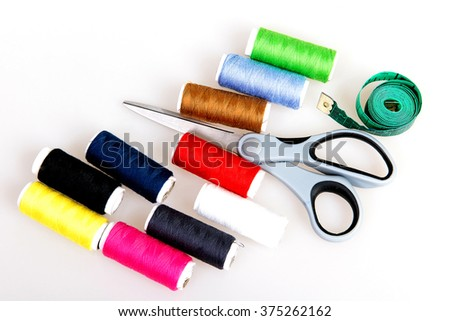 Thread, needles, scissors and meter on a white background, the secrets of needlework, tailoring, sewing workshop, a sewing kit, multi-colored thread in the set - stock photo