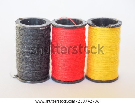 Thread spools of three different colours in the shape of the German flag