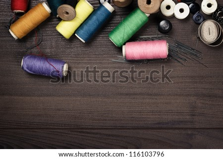 threads buttons and needles on the wooden table - stock photo