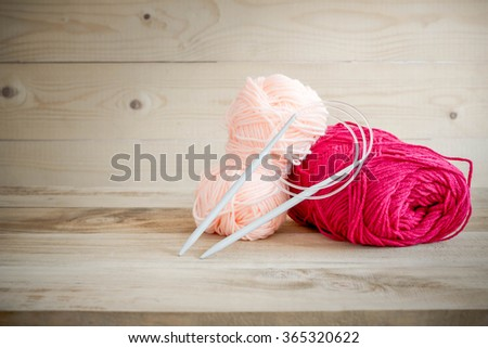 threads for knitting with spokes on wooden table - stock photo