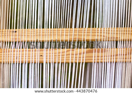 threads on traditional handloom. background of the white threads on the weaving loom - stock photo