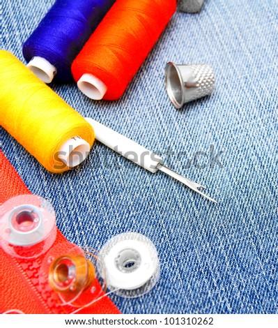 Threads, thimbles, zipper lock on a fabric. - stock photo