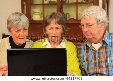 Three active senior citizens surfing the internet. - stock photo