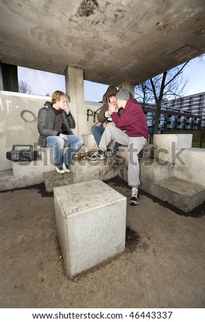 Three adolescent youths lighting cigarettes in a shelter in a suburban area - stock photo