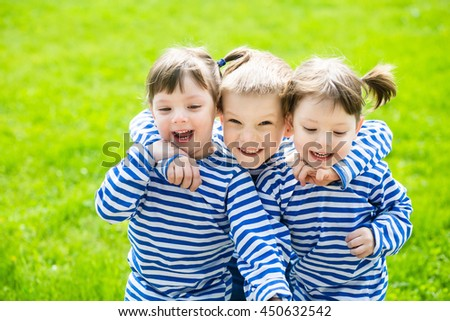 Three adorable little kids in striped T-shirts outdoors at warm summer day - stock photo