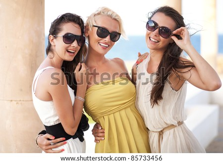 Three adorable women wearing sunglasses - stock photo
