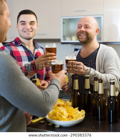 Three adult men drinking beer and laughing at house party - stock photo