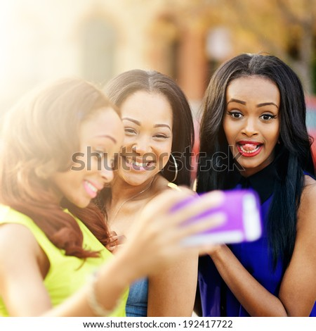 three african girls taking selfies with crazy faces - stock photo