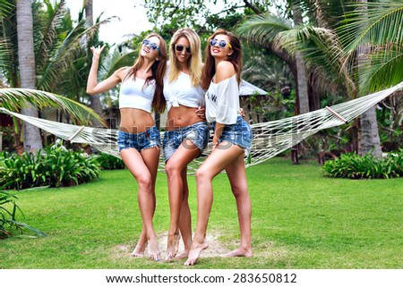 Three amazing stunning fit women with gorgeous long sexy legs posing at tropical garden, wearing trendy mini shorts and simple white tops, friends having fun in summer time, joy, happiness, party. - stock photo