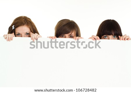Three amusing young girls are hiding on a white background - stock photo