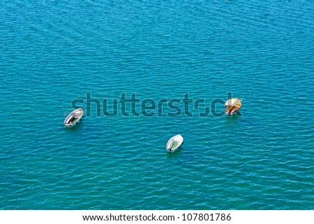 Three anchored boats in water