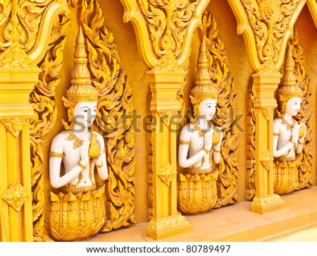Three angels on the walls of the temple - stock photo