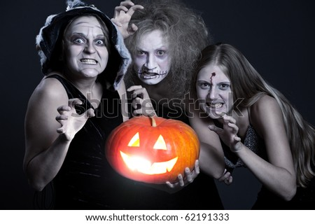 three angry ghost with orange pumpkin over dark background. halloween theme - stock photo