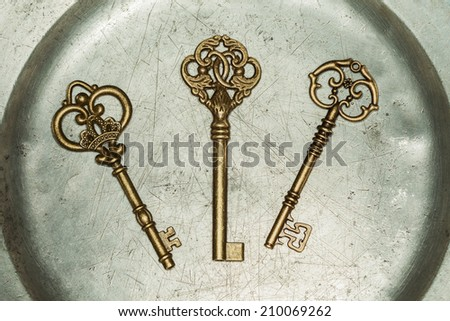 Three antique golden door keys on iron plate - stock photo