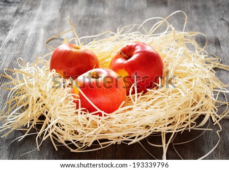 Three apples in straw on a table. - stock photo