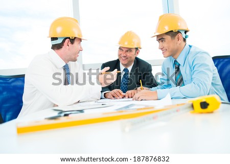 Three architects discussing project of the building - stock photo