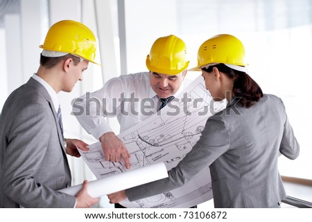 Three architects looking at a project and discussing it - stock photo