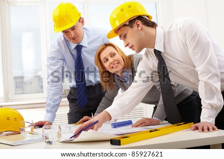 Three architects sitting at table and discussing project - stock photo