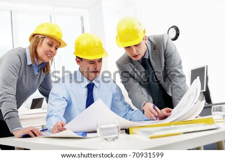 Three architects sitting at table and looking at a project - stock photo