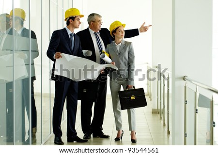 Three architects standing in office building and interacting - stock photo